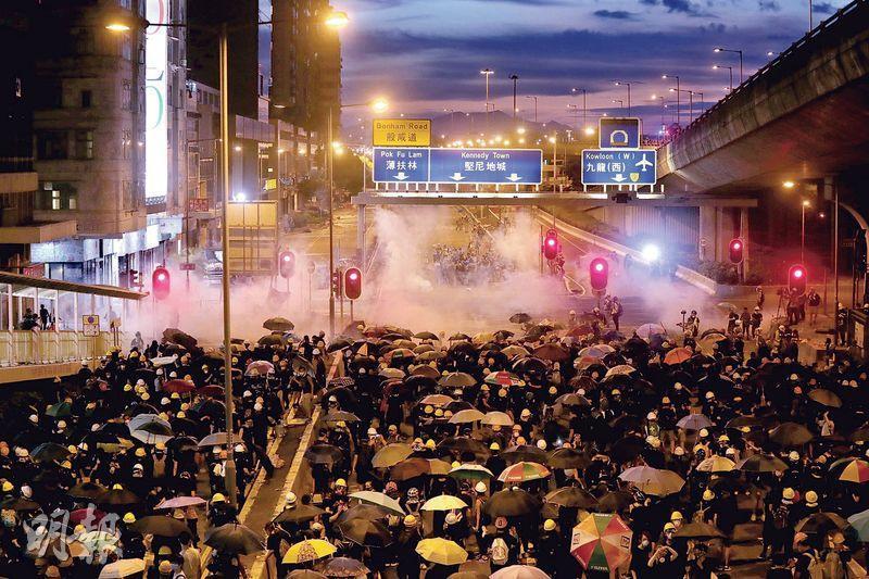 經歷7月21日示威者包圍及衝擊中聯辦(圖左後方)、塗污國徽後,警方昨日在干諾道西重兵佈防,防暴警企滿防線與示威者對峙,並發射多枚催淚彈驅散示威者,不讓人群向前推進半步。(李紹昌攝)