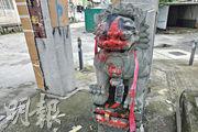 元朗西邊圍牌坊被噴上字句,石獅子亦被淋紅油,附近路面留有溪錢。(張彤攝)