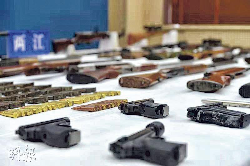 重慶兩江新區警方日前在公安部的統一部署下,破獲「2·14」部督跨省網絡製販槍團伙案,拘捕疑犯35名,繳獲各類槍支39支。圖為警方展示繳獲的槍支和子彈。(網上圖片)