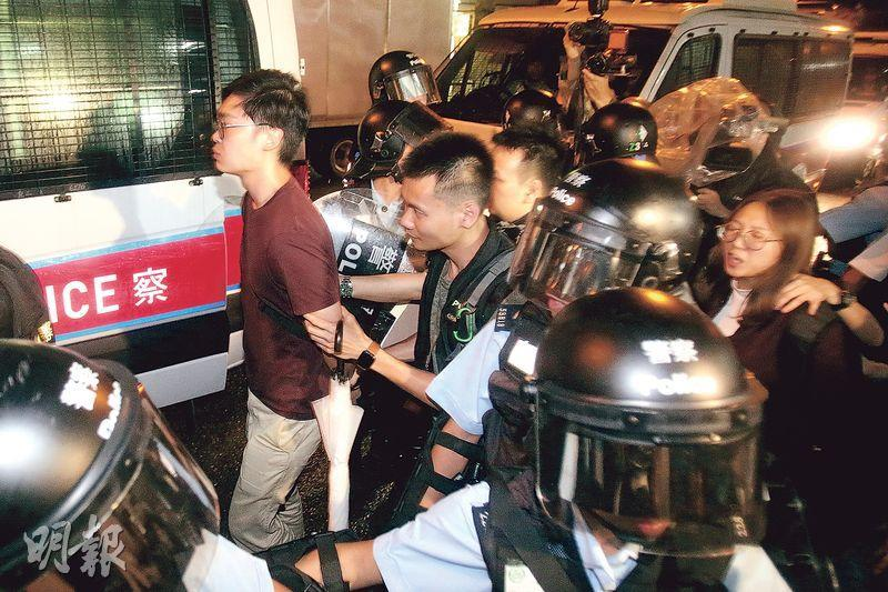 已被取締的香港民族黨,其召集人陳浩天(紅衣者)被鎖上手銬拘捕帶署。(陳惠嫻攝)
