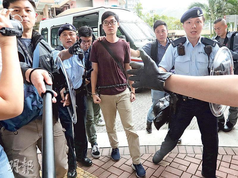 已被取締香港民族黨的召集人陳浩天腰纏鎖鏈,鎖上手銬,由持盾警員押至沙田水泉澳邨清泉樓寓所搜屋。(李紹昌攝)