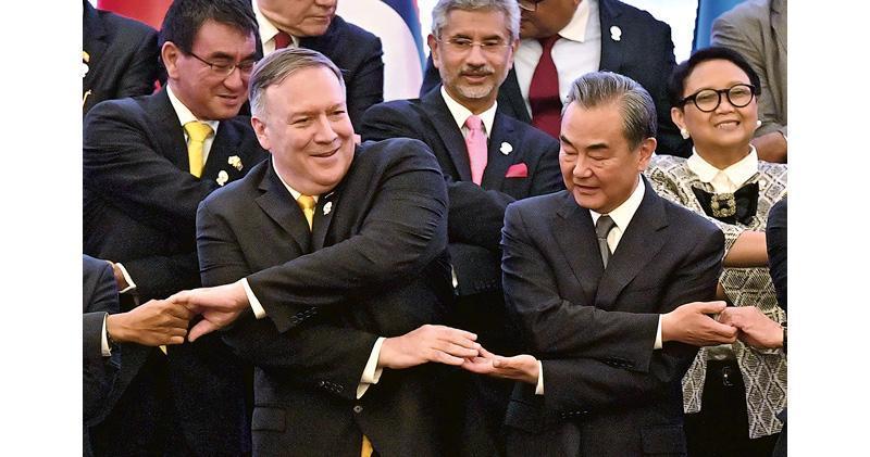 美國總統特朗普周四稱下月1日起將對中國3000億美元商品加徵10%關稅,引來中國國務委員兼外長王毅(前右)的批評;不過昨在東盟外長系列會議期間拍攝大合照,他仍面帶微笑向美國國務卿蓬佩奧(前左)伸出「友誼之手」。(法新社)