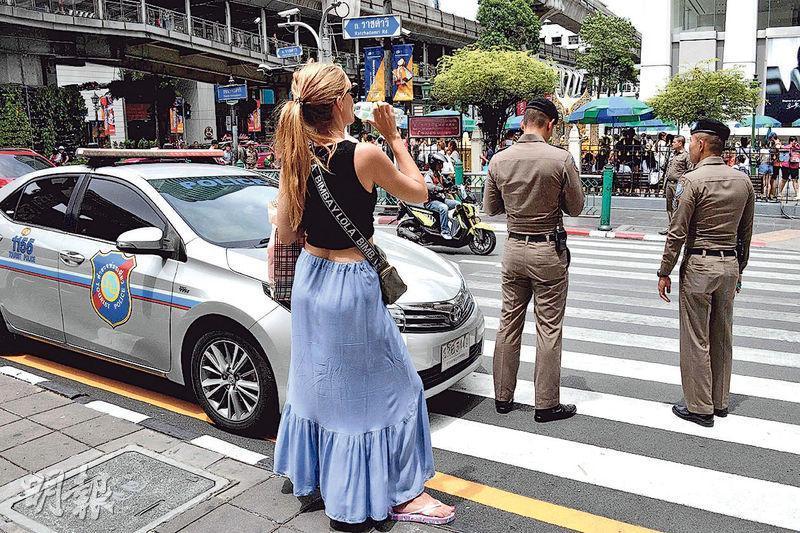 泰國昨日發生多宗小型炸彈案後,曼谷地標四面佛附近有警員駐守。(法新社)