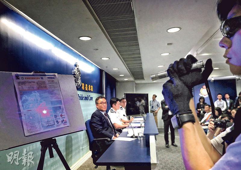 警方昨日以屬案中證物的一支激光筆(警稱「雷射槍」),在不足一米外照射警方刊物《警聲》,約10秒後報紙冒煙。負責示範的警員(右),正是前晚在深水埗拘捕方仲賢的其中一名休班警。(李紹昌攝)