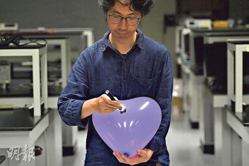 中大物理系高級講師湯兆昇(圖)說,激光照向黑色地方較容易燃燒。他把普通不超過5毫瓦的激光筆照向塗黑了的氣球位置,約一秒後氣球就爆開。(鄧宗弘攝)