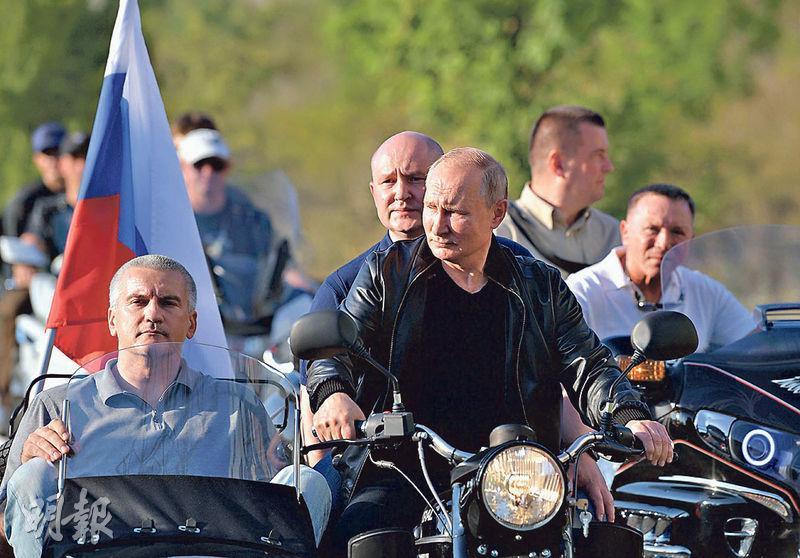 俄羅斯莫斯科上周六有大型反政府示威,總統普京(中)同日在克里米亞的塞瓦斯托波爾市駕駛電單車。(法新社)
