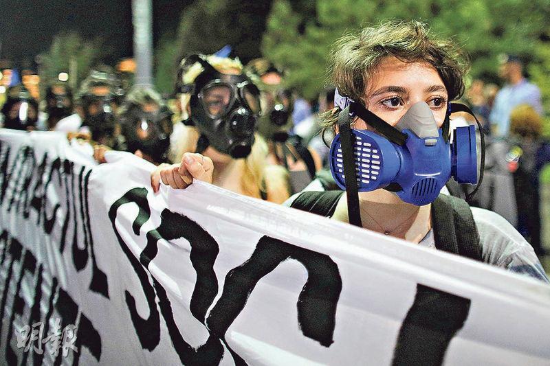 羅馬尼亞人上周六戴上防毒面具示威,紀念防暴警察鎮壓反政府示威1周年。(路透社)
