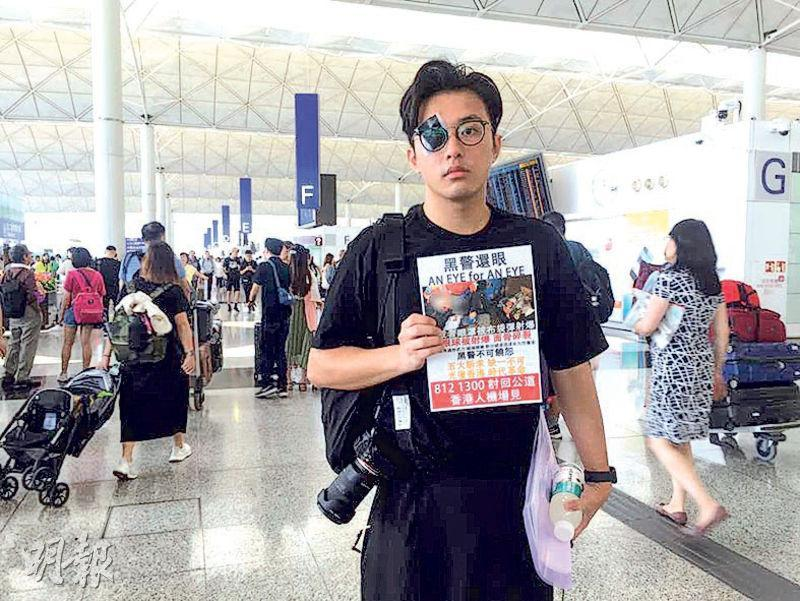 任職廣告業的林先生昨日罷工到機場示威,他用黑紙遮蓋右眼,手持前日女子被打傷眼的照片,在離境大堂層走動。(畢嘉敏攝)