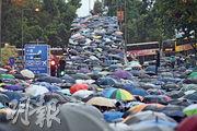 大批市民昨午在暴雨下,身穿黑衣,張開雨傘,參與民陣發起的集會及遊行,前往遊行人潮西至上環、東至炮台山及北角一帶,由於遊行人數太多,遊行者需佔用多條港島區主要幹道前往中環遮打道。下午5時,維園對出的告士打道行車天橋已擠滿人群。(賴俊傑攝)