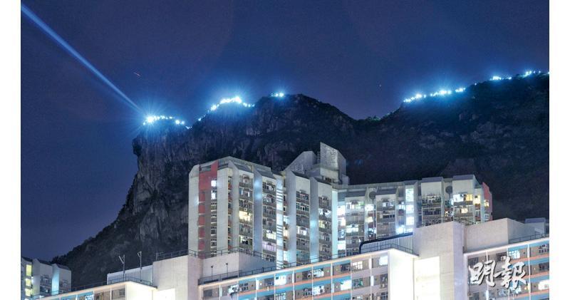 有港人昨晚將「香港之路」的人鏈延綿至獅子山頂,登頂者以電筒燃亮山脊線,「獅子頭」更射出一柱藍光,為象徵港人精神的獅子山增添另一意義。(鍾林枝攝)
