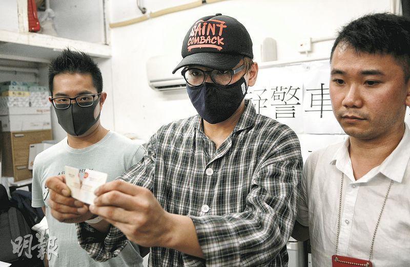 事主梁先生(中)出院後,在區議員麥潤培(右)陪同下見記者,並向傳媒展示被警車撞斷的身分證。(黃煒堯攝)