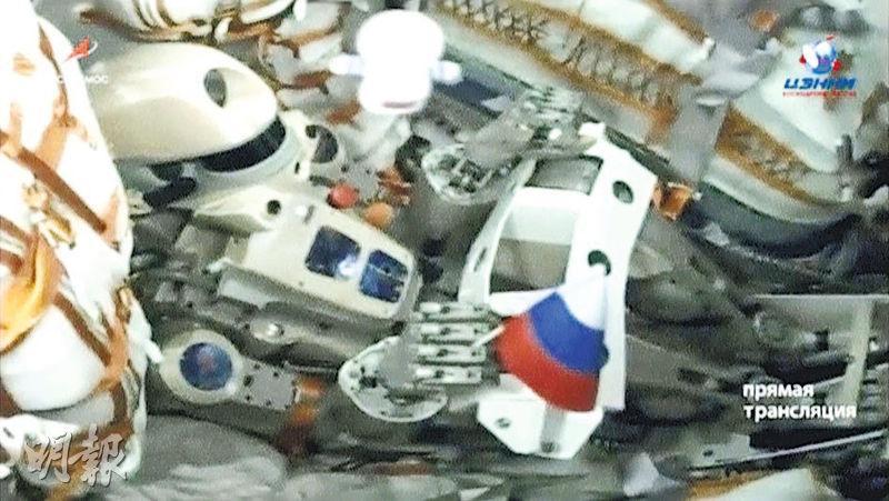 俄羅斯人形機械人「費奧多爾」握着小俄國國旗,坐在「聯合」號太空船內。(路透社)
