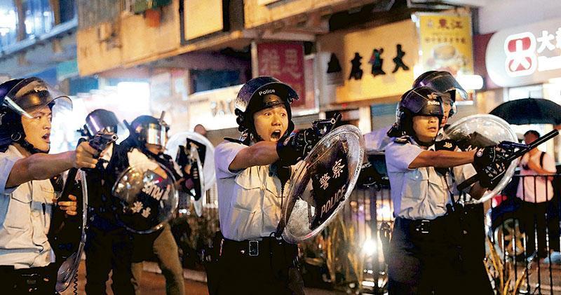 大批手持長棍或疑似鐵通的黑衣人昨晚於沙嘴道與約8至9名持警盾及警棍警員衝突,警員後退,示威者不斷朝警員扔雜物及追打警員,最少4名軍裝警舉起配槍指向人群,有警員一度將手槍指向記者,現場並傳出一下槍聲。(路透社)
