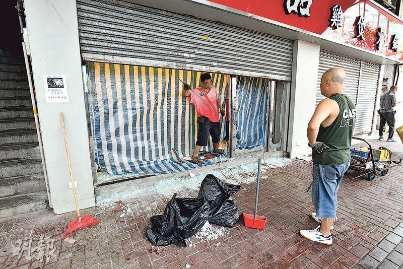 有食肆玻璃門前晚被破壞,玻璃粉碎散落一地,工人昨在場清理。(衛永康攝)
