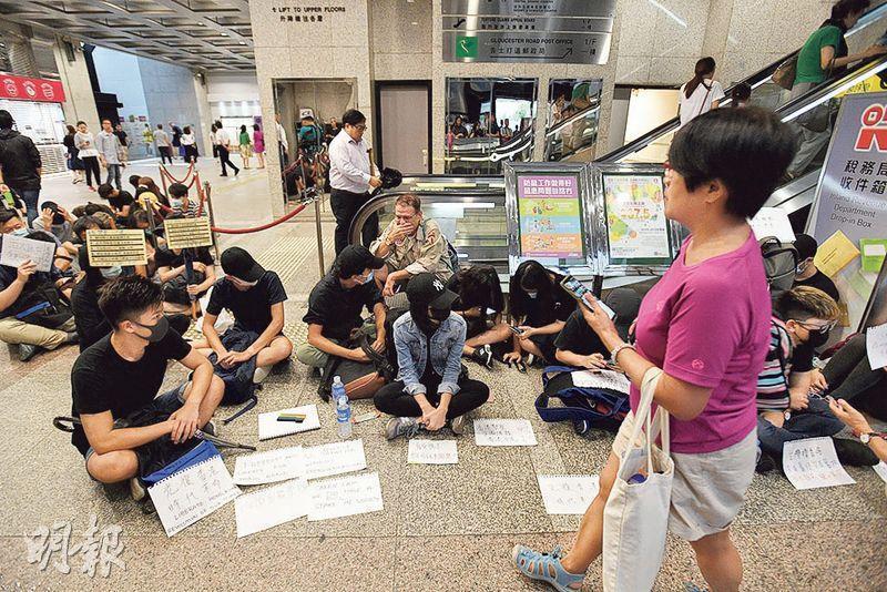 20多名市民昨午到稅務大樓靜坐,示威者讓出通道予人使用,並在紙上寫上字句,有途人停下駐足觀看。(楊柏賢攝)