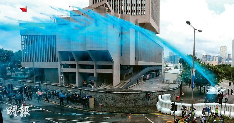 金鐘夏愨道政總外昨日下午衝突期間,警方首次以水炮車向在天橋上(左方,鏡頭外)及地下的示威者發射顏色水劑,地面和橋身均染上藍色。後面建築物為駐軍部隊大廈。(李紹昌攝)