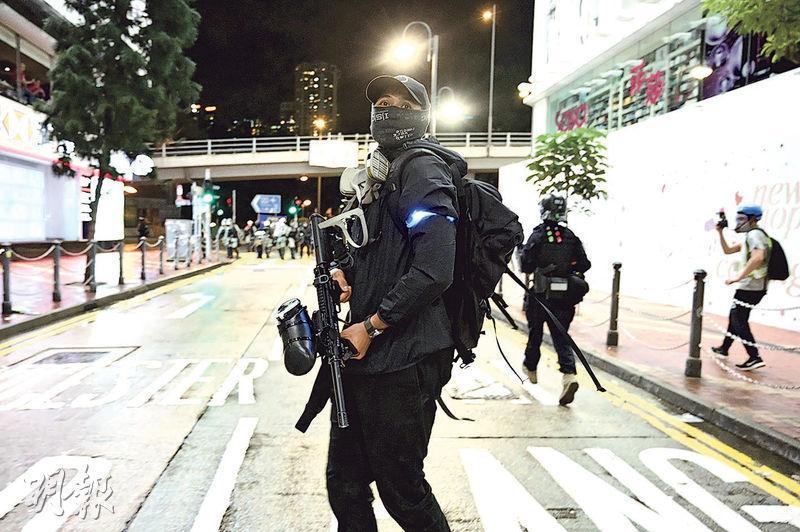 昨晚銅鑼灣皇室堡對出有多名疑似警員,他們戴黑帽、黑口罩,穿黑衣黑褲,又隨身帶有防毒面罩「豬嘴」,其中手持胡椒球槍的男子(圖),左臂有熒光環。(賴俊傑攝)