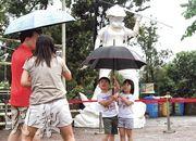 由連登網民眾籌製作的《香港民主女神像》(後)昨日運到中大文化廣場公開展示,女神像一身反修例示威者的裝束,手持寫上「光復香港  時代革命」的旗幟。有人帶着小孩拍照。(劉焌陶攝)
