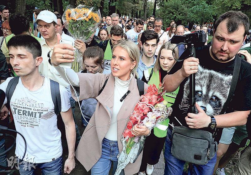 俄羅斯反對派領袖之一的索博利(舉手機者)昨日與示威者一起遊行。(路透社)