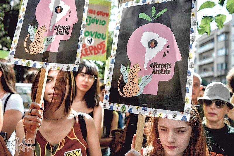 環保人士昨在希臘雅典的巴西大使館外集會,要求當局採取行動拯救亞馬遜雨林。(法新社)