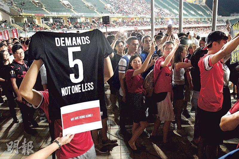 世界盃亞洲區外圍賽香港對伊朗球賽中場休息時,大批香港球迷在看台築起人鏈。有球迷舉起一件印有「5 DEMANDS NOT ONE LESS」的T恤,表達「五大訴求缺一不可」。(楊柏賢攝)