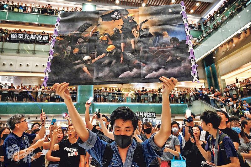 逾百人聚集沙田新城市廣場大合唱《願榮光歸香港》,其中一人高舉一幅示威者的畫像,畫像構圖猶如紀念法國大革命的油畫《自由領導人民》。(賴俊傑攝)