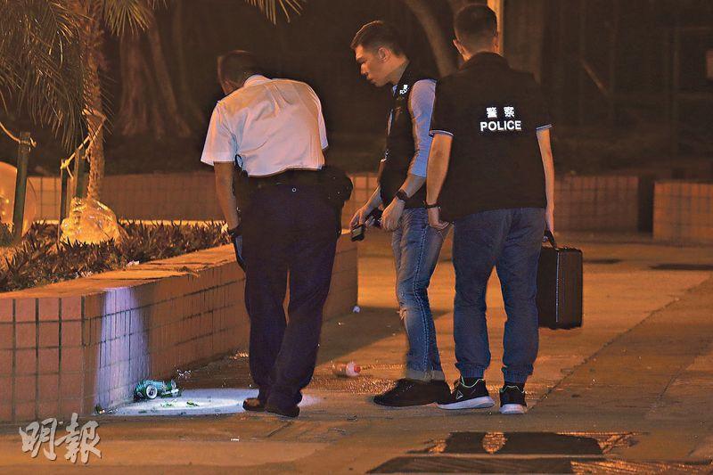 疑載有腐液的玻璃樽從高處墜下濺傷6人,探員事後在鴨脷洲邨現場調查及蒐證。(伍浦鋒攝)
