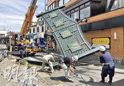 強颱風「法茜」周一吹襲日本,為關東地區帶來破紀錄強風暴雨,其間神奈川縣鎌倉市有工人嘗試移走被強風吹倒的招牌。(法新社)