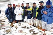 英國首相約翰遜(白衣者)上周五到訪蘇格蘭,在彼德赫德魚市場與工人交流。(法新社)