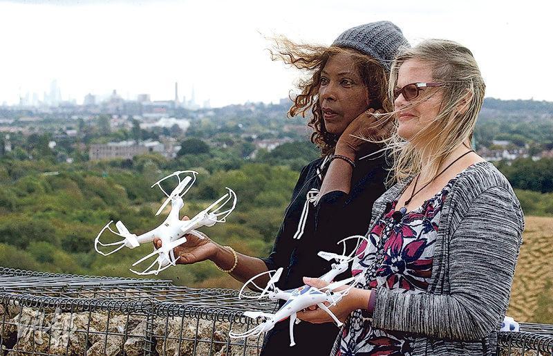 環團「希斯路暫停」周五放無人機干擾機場失敗。圖為兩名組織成員周四在機場附近手持玩具無人機合照。(路透社)