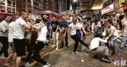 炮台山昨晚有操內地口音或普通話男子聚集,手持摺櫈、 長通(圖中右方)襲擊經過的年輕人,其間數名男子圍住一名市民,另一面有人跌倒。現場有人勸阻,初時未見警方介入,其後防暴警前來分隔。(曾憲宗攝)