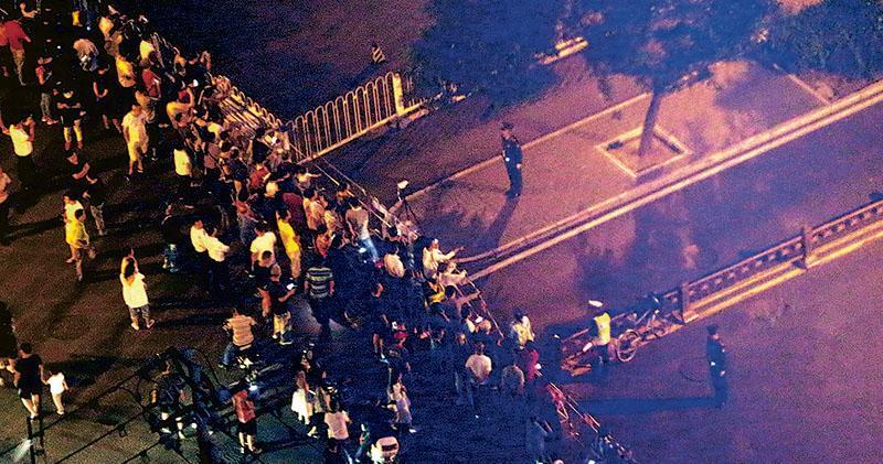 因國慶綵排需要,北京天安門區域多個路段近期多次實施交通管制。圖為上周六(14日)晚不少市民圍在被封路的路段觀望。(路透社)