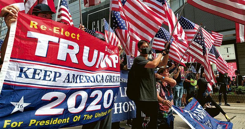 本港昨日遊行期間,有示威者揮舞美國國旗和舉起支持美國總統特朗普連任的標語,促請美國政界支持就《香港人權與民主法案》立法。(曾憲宗攝)