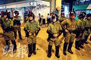 在元朗西鐵站的連儂牆,數人在防暴警察築起的防線後方撕紙。該批人其後在警方護送下登上警車離開。(路透社)