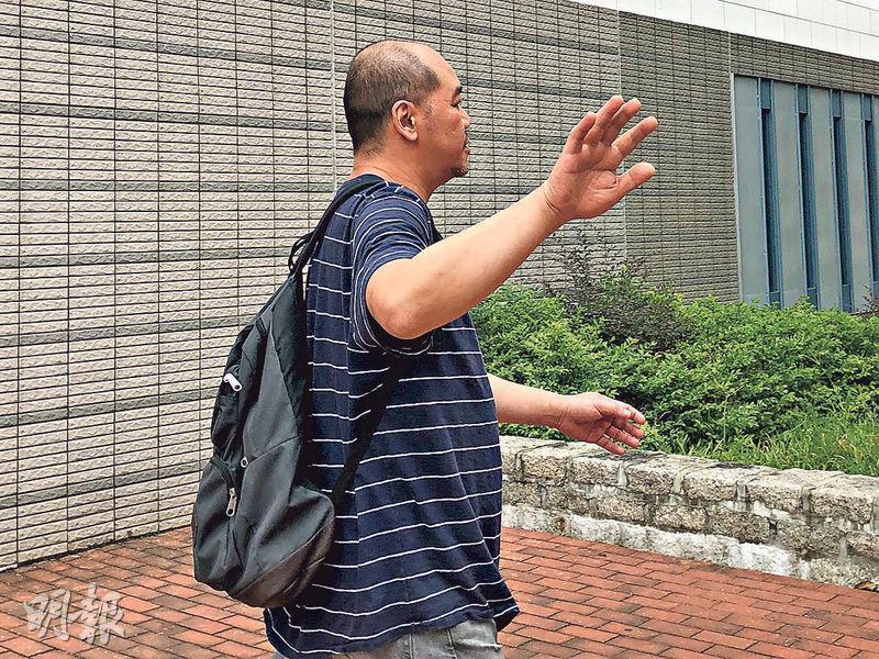 被告陳耀鈞被指拳打警長,他昨到西九龍裁判法院提訊,離開法院時一度以手遮面,並說「唔係我呀」。(方嘉蓓攝)