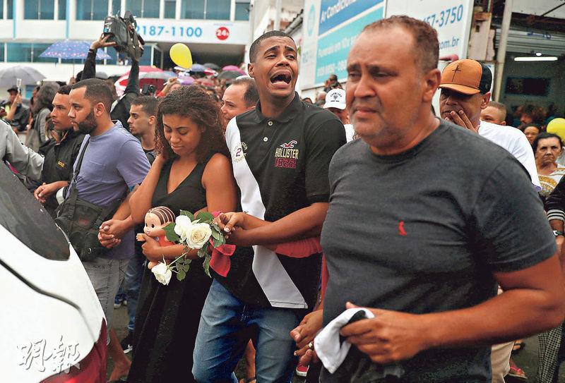 在巴西里約熱內盧警方行動中遇害的女童費利什周日出殯,其祖父(右起)、叔叔、母親一臉愁容。(路透社)