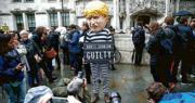 英國最高法院11名法官昨日一致裁定,首相約翰遜建議英女王暫停國會的做法違法,聆訊後有示威者打扮成穿囚衣的約翰遜,在最高法院門外手持「約翰遜有罪」的標語牌。(路透社)