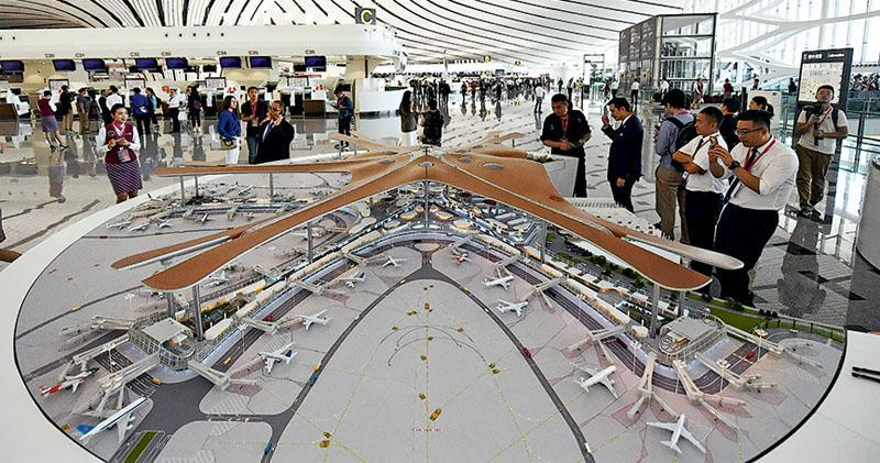 北京大興國際機場昨日正式啟用,航站樓內擺放的機場航站樓模型,吸引許多人駐足觀看。(新華社)
