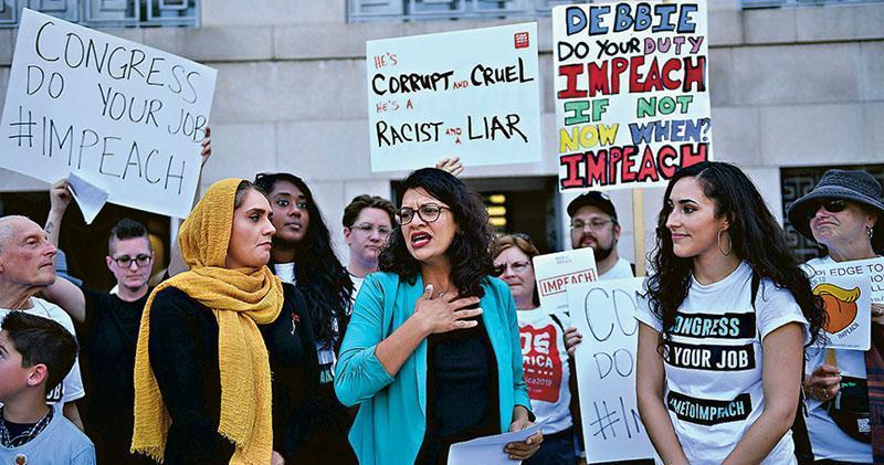 美國華盛頓周一有示威者聚集在國會山莊前,要求眾議院對總統特朗普展開彈劾調查,其間密歇根州的民主黨眾議員特萊布(中)亦有參與。(法新社)