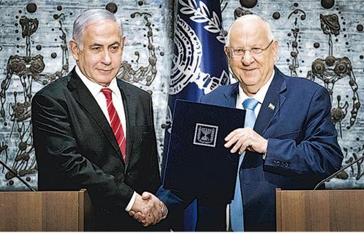 以色列總理內塔尼亞胡(左)周三在耶路撒冷獲總統里夫林(右)授權籌組新一屆政府。(新華社)