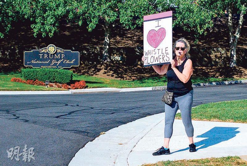 一名示威者前天手持「我愛爆料者」的標語牌,在弗吉尼亞斯特靈的高爾夫球場外向特朗普抗議。(法新社)