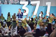奧地利人民黨周日勝出選舉,黨魁庫爾茨(左)在維也納的黨總部與支持者慶祝,他背後人士手持「37.1」字牌,代表初步票站出口調查顯示的人民黨得票率。(法新社)