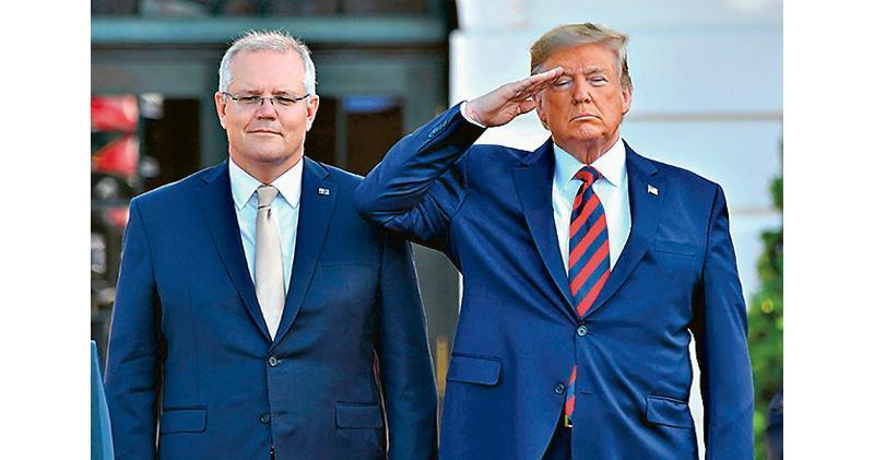 澳洲總理莫里森(左)上月到訪白宮,美國總統特朗普(右)在儀式上敬禮。(法新社)
