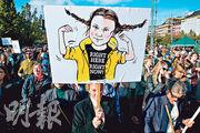 瑞典首都斯德哥爾摩上周五有要求政府推動環保的集會,一名示威者舉起環保少女通貝里的卡通化海報。(法新社)
