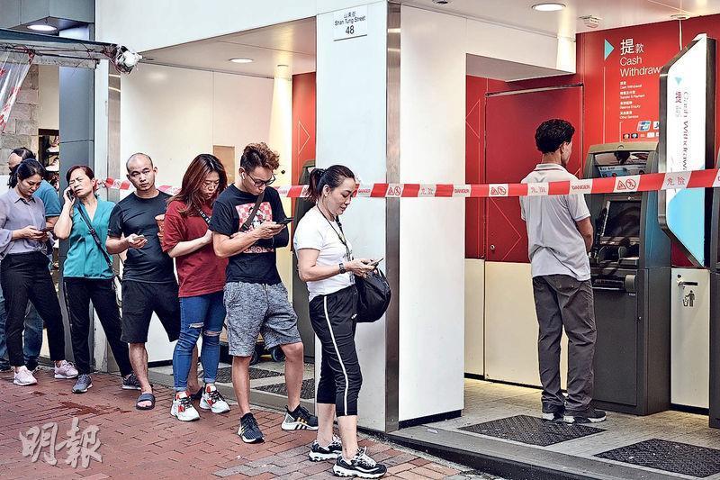 旺角山東街中銀香港多部自動櫃員機被嚴重破壞,有市民發現其中一部提款機雖然玻璃屏幕損毁,仍可提取現金,於是在封鎖線外排隊提款。(賴俊傑攝)