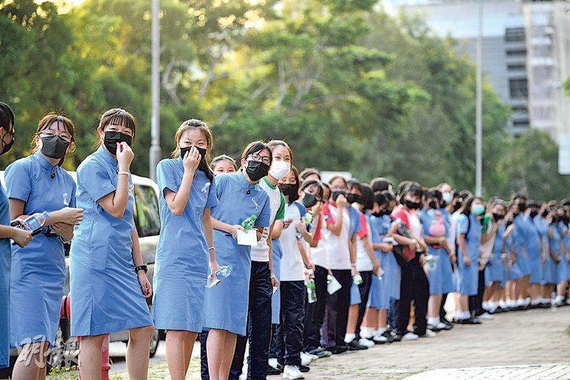 政府實施《禁蒙面法》,又要求學校呈報今日學生戴口罩情况,有學生發起今日戴口罩回校「抗命」。圖為早前有學生在九龍塘戴口罩築人鏈,爭取五大訴求。(資料圖片)