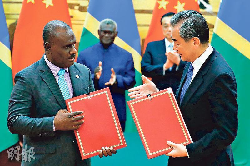 國務委員兼外交部長王毅(右)昨日在人民大會堂與所羅門外長馬內萊勒出席兩國有關協議簽字儀式。(法新社)
