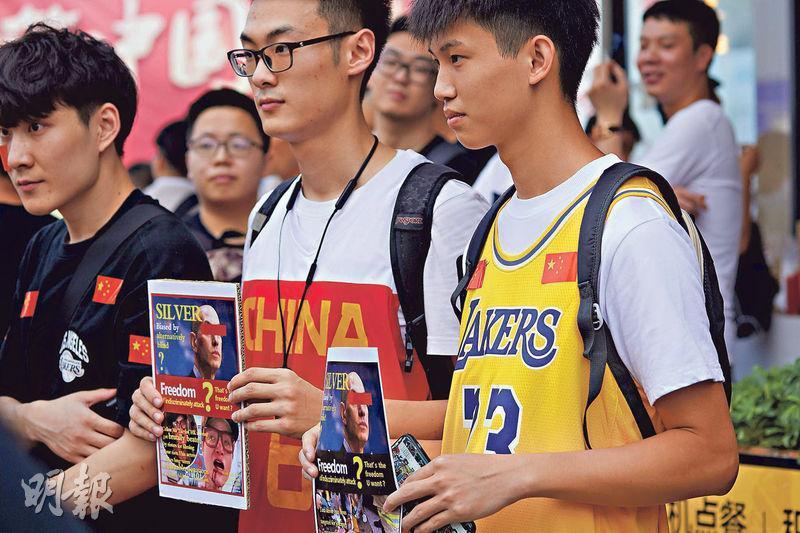 中國籃球迷在10月12日於深圳市舉行,由洛杉磯湖人隊對布魯克林籃網隊的NBA季前賽前,舉起反對NBA總裁亞當‧施華(Adam Silver)言論的標語。(法新社)