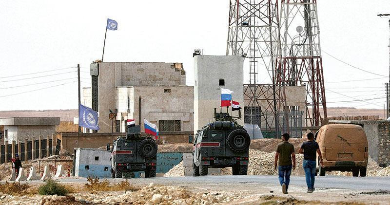 掛着俄羅斯與敘利亞國旗的軍車昨日駛至敘利亞北部城鎮曼比季(Manbij)。(路透社)