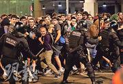 西班牙防暴警察周一晚在巴塞隆拿的機場,揮警棍驅散抗議加泰隆尼亞獨立運動領袖被判囚的示威者。(路透社)